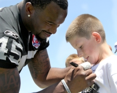 KAT MINER, SPECIAL TO THE DAILY PRESS Hesperia High Alumni Marcel Reece signs a t-shirt for one of several kids that participated in the inaugural Marcel Reece Youth Football Skills Camp held at Hesperia High School on Saturday. Reece said he wanted to run his camp in the High Desert because of the absence of this kind of event in the area. He hopes to make it an annual event.