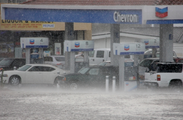 KAT MINER, SPECIAL TO THE DAILY PRESS Motorists attempt to keep dry while gassing up at the Cajon Summit Chevron station. The summer cloudburst hit the area about 3pm, Saturday afternoon. The rain did little to cool the hot temperatures that have been plaguing the area all week. Temperatures above 100 degrees are expected to continue through Monday.