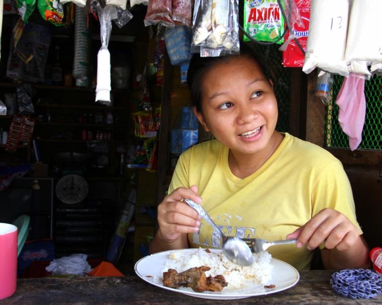 Sari Sari store clerk enjoying lunch and conversation